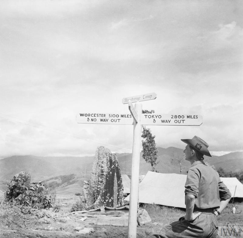 A member of the Worcestershire Yeomanry views an amusing roadsign beside an ancient standing stone at 'Stonehenge Camp' on the Imphal to Kohima road. The sign reads 'Worcester, 5100 miles & No Way Out' and 'Tokyo, 2,800 miles & Way Out', November 1944.