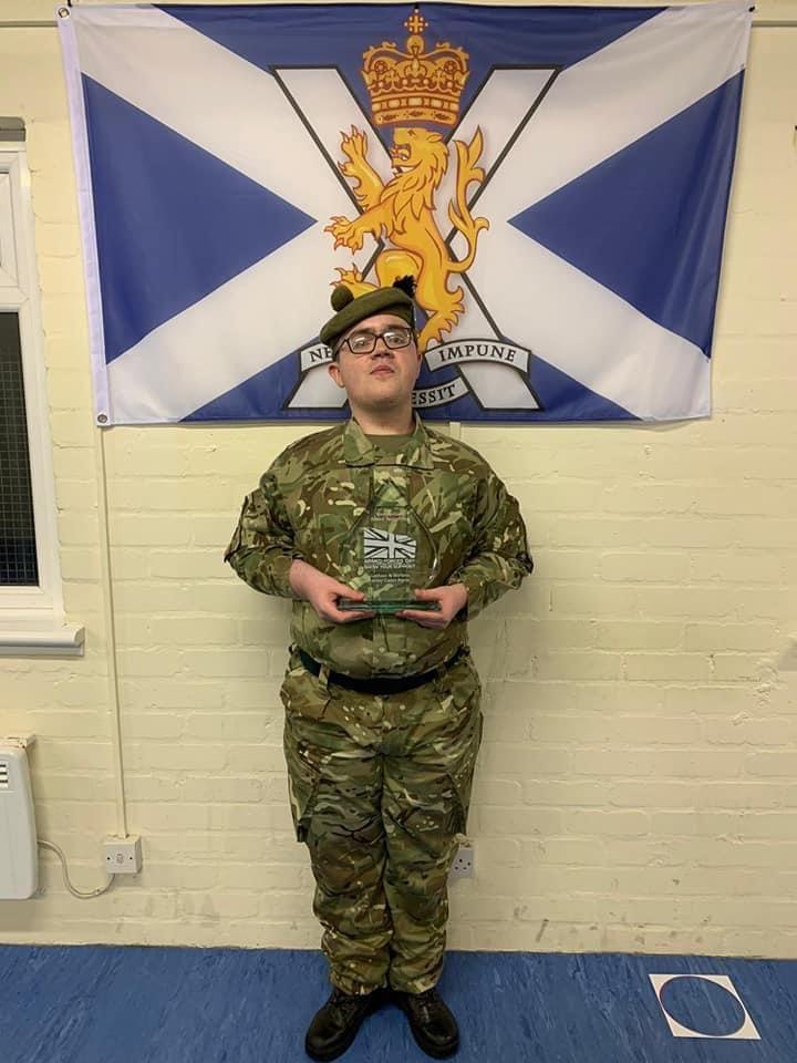 Teenager standing holding award