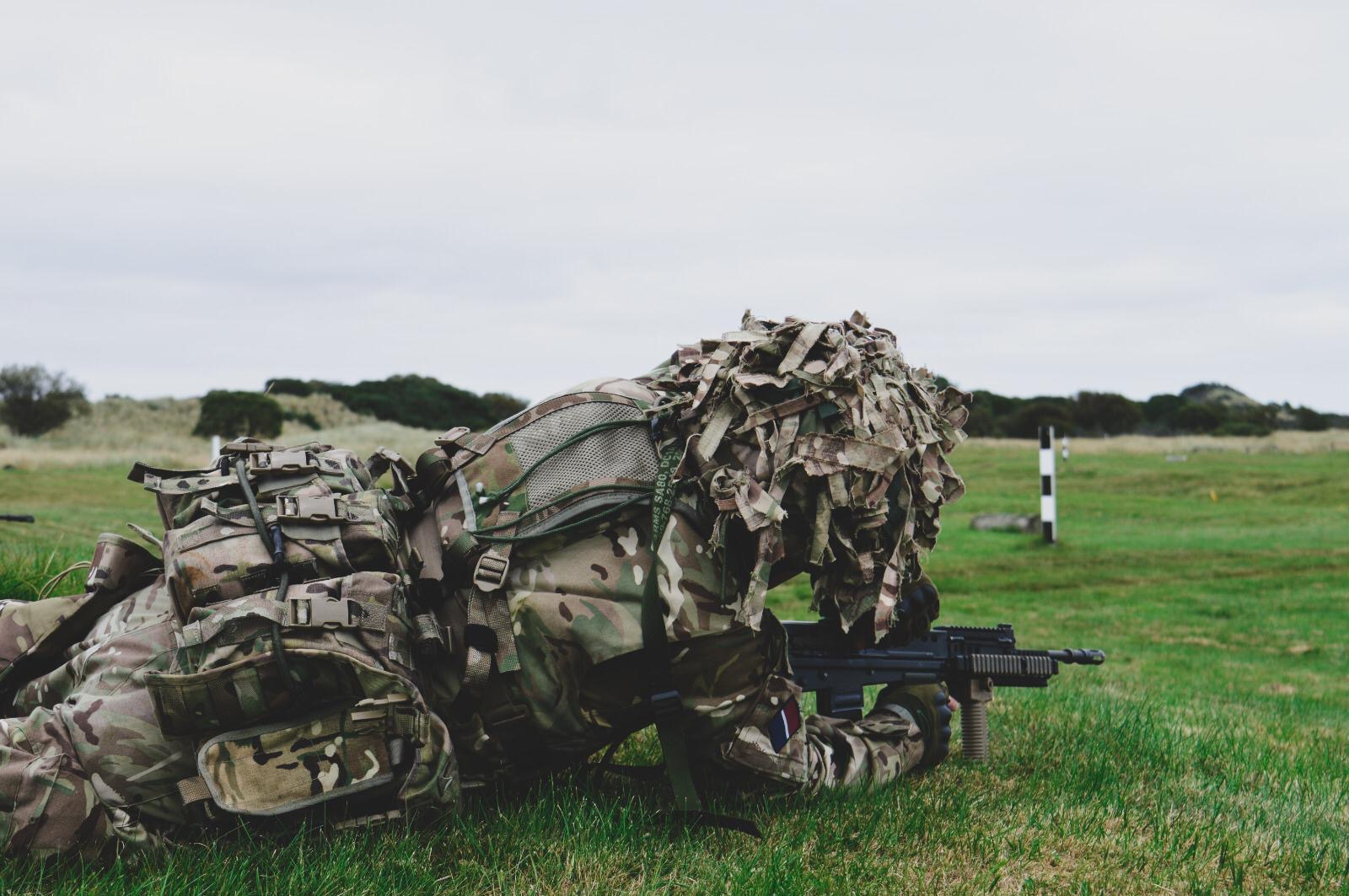 Soldier dressed in camouflage on grass with gun