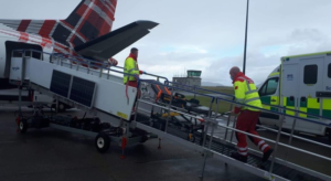 Two men pushing an aid bed in a plane via a ramp