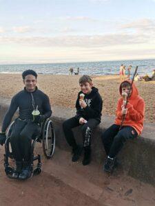 Three boys sit by the beach