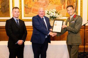Three gentlemen in formal wear with certificate