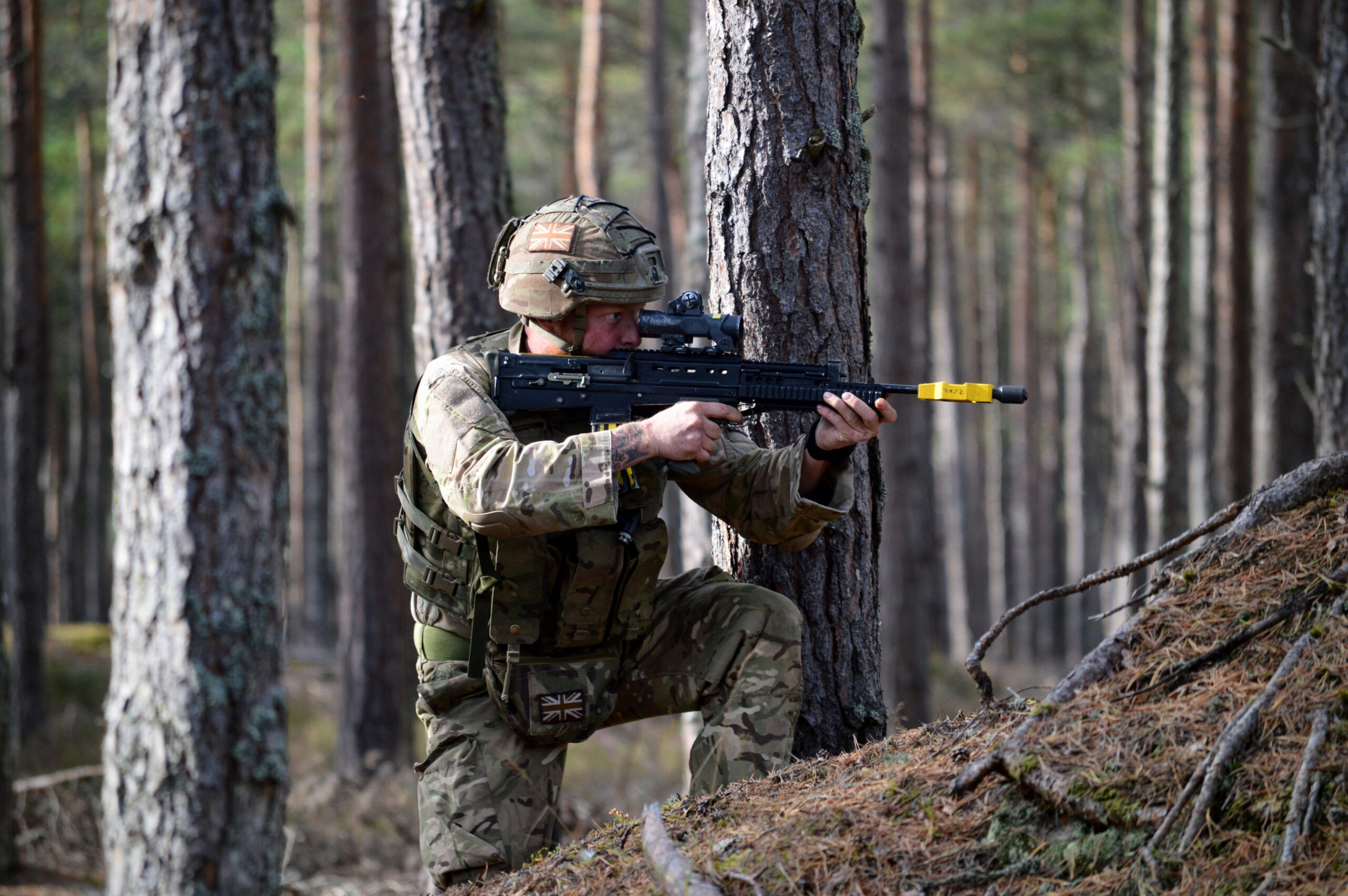Man dressed in camouflage crouching holding gun